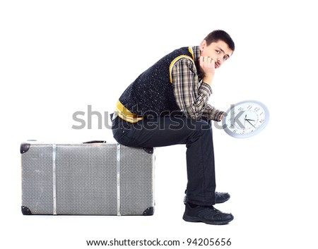 Young man waiting at airport, holding big clock, isolated over white - stock photo
