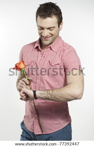 young man waiting for his date holding a rose - stock photo