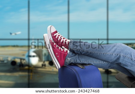 young man waiting for the plane at an airport - stock photo
