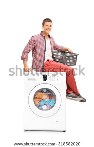 Young man waiting for the washing machine to finish seated on top of it and holding an empty plastic basket isolated on white background