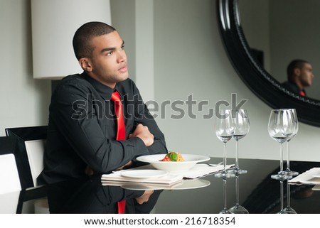 young man waiting in restaurant and thinking. guy sitting at table with wineglasses and looking up - stock photo
