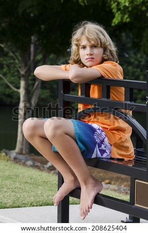 young man waiting on a bench for his ride to pick him up - stock photo