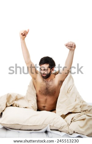 Young man waking up in bed and stretching his arms - stock photo