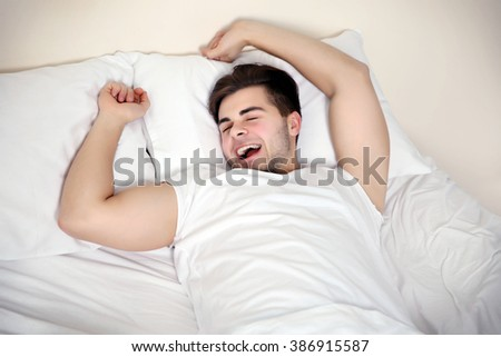 Young man waking up in bed at home