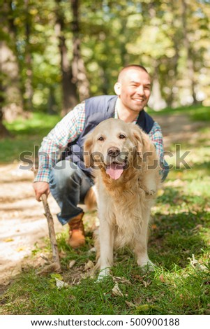Young man walking a dog at the park in good weather. Boy and golden retriever. Autumn environment