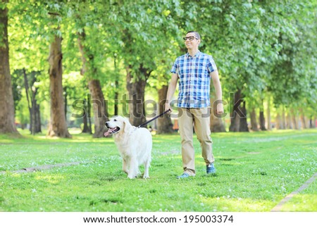 Young man walking his pet dog outdoors  - stock photo