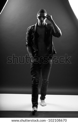 Young man walking in darkness - stock photo