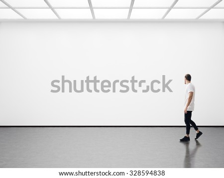 Young man walking in the empty gallery - stock photo