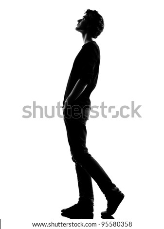 young man  walking looking up silhouette in studio isolated on white background - stock photo