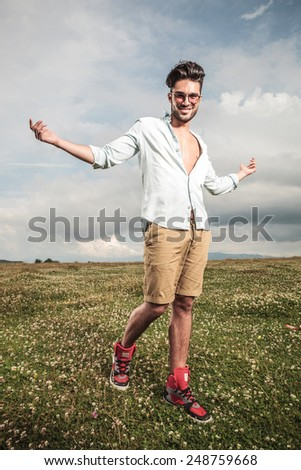 Young man walking on a field with flowers with his arms open, smiling and looking at the camera. - stock photo