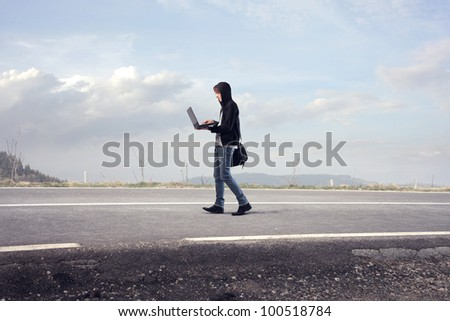 Young man walking on a road and using a laptop - stock photo