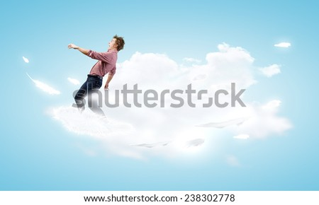 Young man walking on cloud high in sky - stock photo