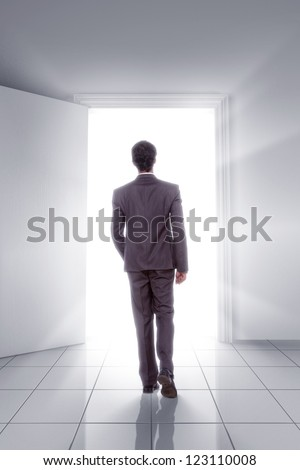 young man walking towards open door showing opportunity - stock photo