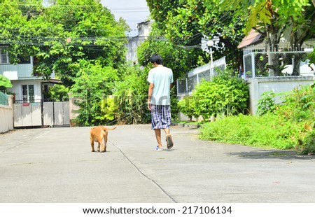 Young man walking with his dog on the street  - stock photo