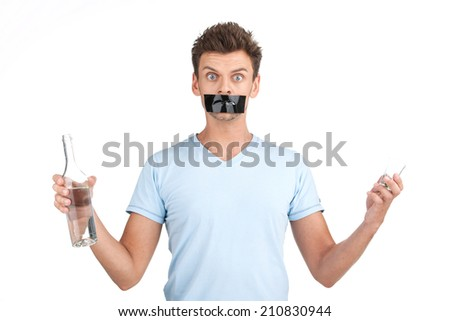 young man wants to stop drinking. waist up of man with bottle of alcohol and tape over mouth.  - stock photo