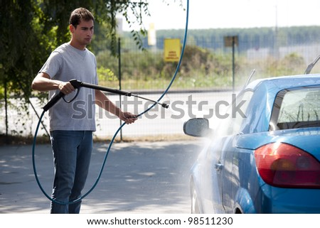 Young man washing his car with compression water - stock photo