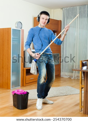 Young man washing parquet floor with mop in home