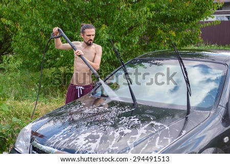 Young man washing the car near the house