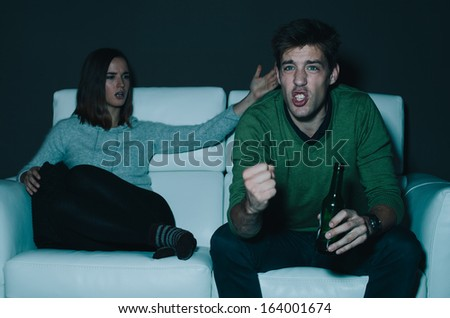 Young man watching a game his girlfriend is annoyed with him and shouting - stock photo