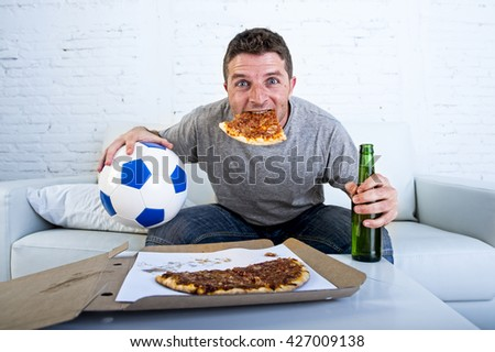 young man watching football game on television celebrating goal crazy happy jumping on sofa couch at home with ball beer bottle and pizza in his mouth looking excited and cheerful - stock photo