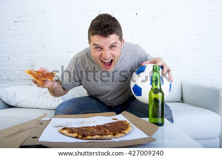 young man watching football game on television celebrating goal crazy happy sitting on sofa couch at home holding and pizza with beer bottle looking excited and cheerful - stock photo