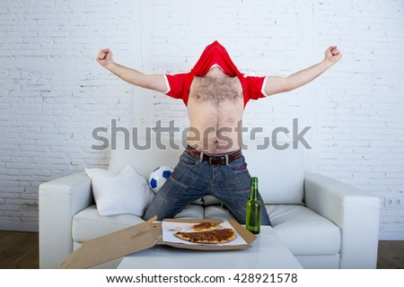 young man watching football game on television celebrating goal crazy with jersey on his head jumping on sofa couch at home with ball holding  beer bottle eating pizza excited - stock photo