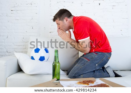 young man watching football game on television nervous and excited suffering stress praying god for goal on sofa couch at home with ball , beer bottle and  pizza looking crazy anxious - stock photo