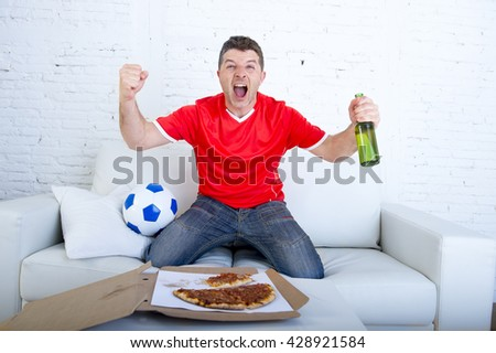 young man watching football game on television wearing team jersey celebrating goal crazy happy jumping on sofa couch at home with ball holding  beer bottle eating pizza excited - stock photo