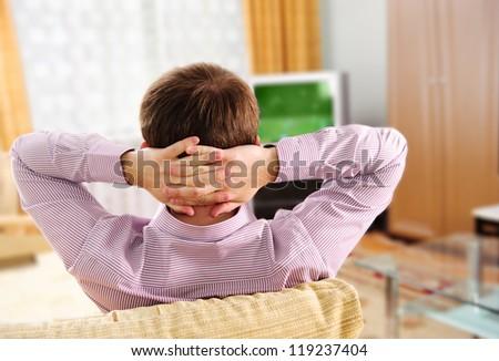Young man watching football game via tv at home - stock photo