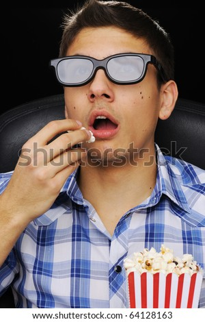 Young man watching movie in 3D glasses at cinema - stock photo