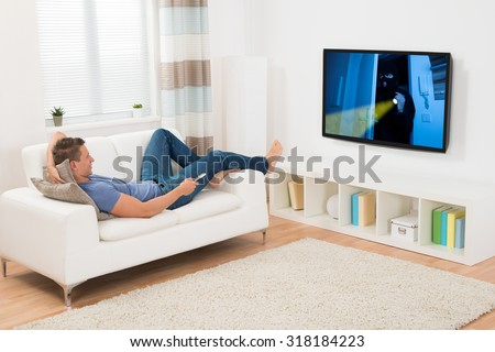 Young Man Watching Movie On Television In Living Room