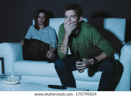 Young man watching sports on TV girlfriend fed up with him - stock photo