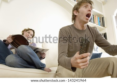 Young man watching television and cheering with woman reading magazine on sofa - stock photo