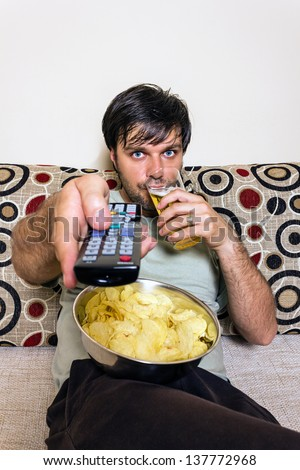 Young man watching television, eating potato chips and drinking beer indoor - stock photo