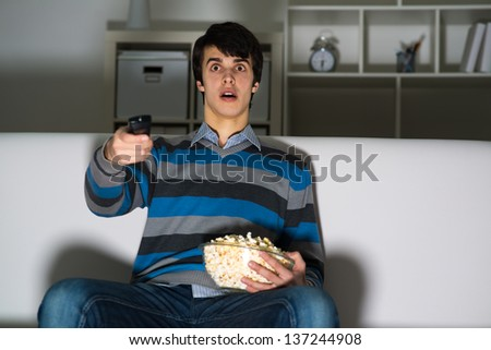young man watching television with popcorn, remote control switches channels - stock photo