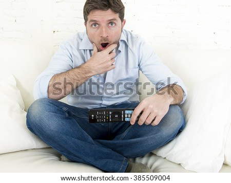young man watching tv sitting at home living room sofa holding remote control looking intense and very interested enjoying television program or movie in disbelief amazed and shock face expression - stock photo