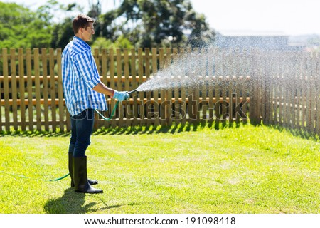 young man watering backyard lawn using hosepipe - stock photo