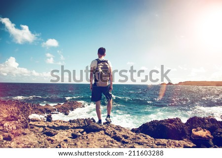 Young man wearing a backpack standing on rocks overlooking the ocean looking down at the white surf in contemplation backlit by the flare of a hot tropical sun - stock photo