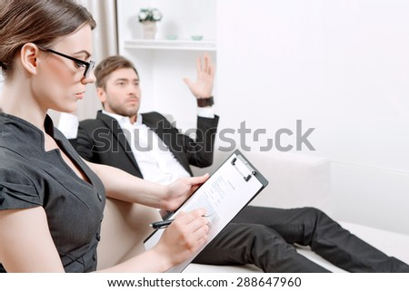 Young man wearing a black suit lying on a couch telling his problems and gesticulating, psychologist with clipboard listening to him and making notes during therapy session, selective focus - stock photo