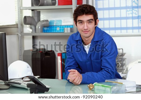 young man wearing a blue jumpsuite at office