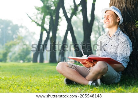 young man wearing a hat reading a book in the park - stock photo