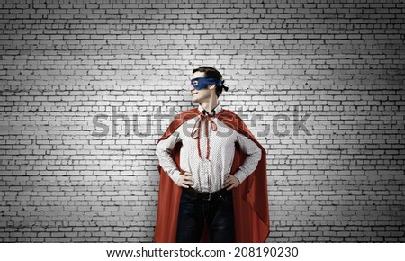 Young man wearing a mask and cape - stock photo