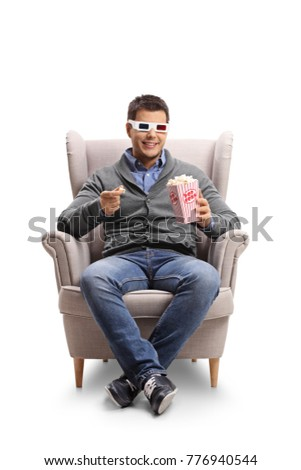 Young man wearing a pair of 3D glasses sitting in an armchair and having popcorn isolated on white background