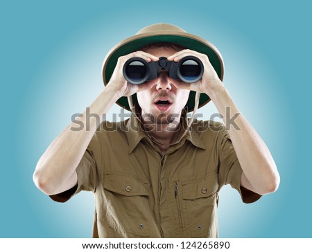 Young man wearing a pith helmet looking through a pair of binoculars with a surprised expression, on blue background - stock photo