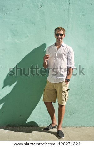Young man, wearing a white shirt and smoking a cuban cigar, standing in the bright sunlight against a mint green painted, plastered wall - stock photo