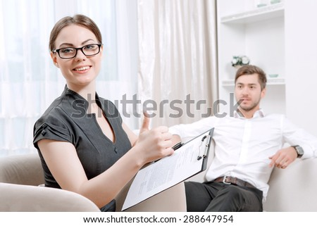 Young man wearing a white shirt sitting on a couch smiling, psychologist with clipboard looking at us happily holding a clipboard in her hands during therapy session, selective focus - stock photo