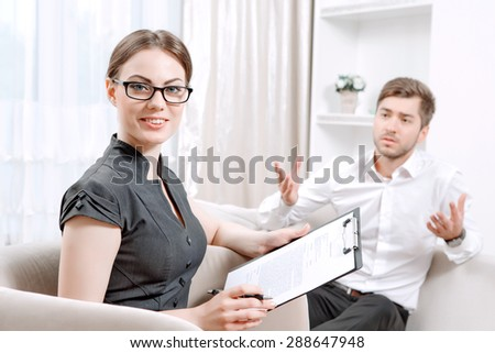 Young man wearing a white shirt sitting on a couch telling his problems and gesticulating, psychologist with clipboard listening to him and looking at us during therapy session, selective focus - stock photo