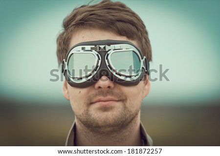 Young man wearing aviator motorcycle glasses at the airfield