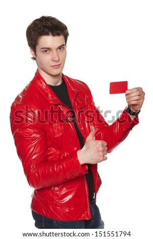Young man wearing bright red jacket showing blank credit card, gesturing thumb up, over white background - stock photo