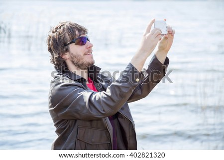 Young man wearing brown leather jacket and sunglasses holding mobile phone, making a selfie on the phone.  Man on the sea background.